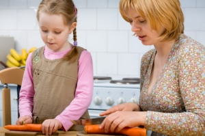 Daughter and mother prepare meal in kitchen