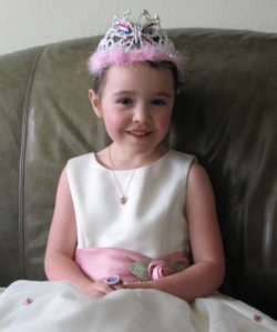 Girl sitting in a princess dress and tiara in article about young girls and their looks