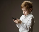 17748588-boy-playing-game-on-cell-phone-kid-holding-mobile-on-grey-background